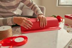 Un hombre que envuelve los regalos en cinta roja y rosas frescas valentines fotografía de archivo