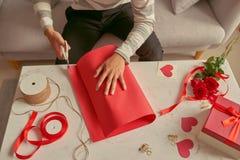 Un hombre que envuelve los regalos en cinta roja y rosas frescas valentines foto de archivo