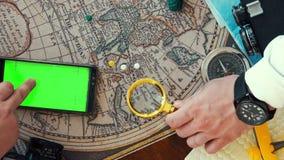 Un hombre que estudia cuidadosamente un mapa que miente en la tabla con una lupa, la segunda en este tiempo que hojea con almacen de metraje de vídeo