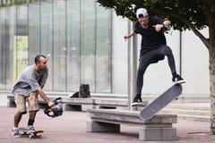 Un hombre que filma a un skater que hace un tirón en un banco foto de archivo