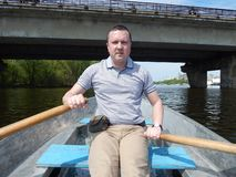 Un hombre que flota en un barco monta con fotografía de archivo