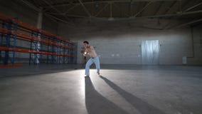 Un hombre que hace diversos elementos del capoeira en el cuarto con el piso concreto, las paredes de ladrillo y la luz brillante almacen de metraje de vídeo