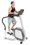 Un hombre que hace ejercicio de la máquina del paso de progresión Fotografía de archivo