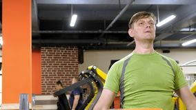 Un hombre que hace un ejercicio en el delta trasero con las pesas de gimnasia que se sientan con un apret?n recto en un estudio d almacen de video