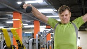 Un hombre que hace un ejercicio en el delta trasero con las pesas de gimnasia que se sientan con un apret?n recto en un estudio d metrajes