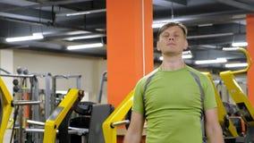 Un hombre que hace un ejercicio en el delta trasero con las pesas de gimnasia que se sientan con un apret?n recto en un estudio d almacen de metraje de vídeo