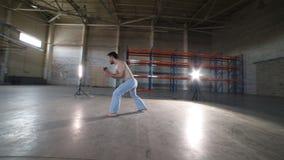 Un hombre que hace elementos del capoeira en el cuarto con el piso y las paredes de ladrillo concretos almacen de metraje de vídeo