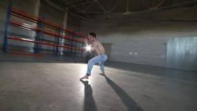 Un hombre que hace elementos difíciles del capoeira en el cuarto con el piso y las paredes de ladrillo concretos metrajes