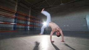 Un hombre que hace los elementos del capoeira - un cartwheel - en el cuarto con el piso concreto, las paredes de ladrillo y la lu almacen de metraje de vídeo
