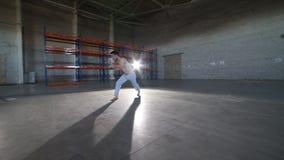 Un hombre que hace los elementos del capoeira - un cartwheel - en el cuarto con el piso y las paredes de ladrillo concretos almacen de video