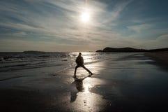 Un hombre que hace un kata en la playa Foto de archivo libre de regalías
