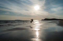 Un hombre que hace un salto del tecleo del talón en el lado izquierdo en la playa Fotos de archivo