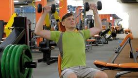 Un hombre que hace una prensa de banco con las pesas de gimnasia que se sientan con un apret?n recto en un estudio de la aptitud metrajes