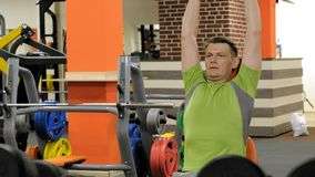 Un hombre que hace una prensa de banco con las pesas de gimnasia que se sientan con un apret?n recto en un estudio de la aptitud almacen de metraje de vídeo