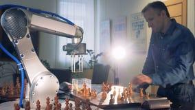 Un hombre que juega a ajedrez con una mano robótica almacen de video