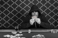 Un hombre que juega el póker que se sienta en una tabla fotos de archivo libres de regalías