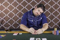 Un hombre que juega el póker que se sienta en una tabla imagenes de archivo