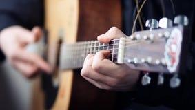 Un hombre que juega en una guitarra acústica de madera hermosa foto de archivo libre de regalías