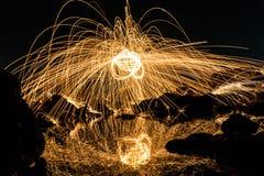 Un hombre que juega las lanas de acero en la playa Fotos de archivo