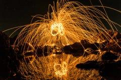 Un hombre que juega las lanas de acero en la playa en la noche Foto de archivo
