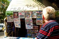 Un hombre que lee los periódicos en Atenas, Grecia Imágenes de archivo libres de regalías