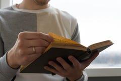Un hombre que lee un libro, controles él en sus manos Imagen de archivo