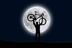 Un hombre que levanta una bici en el frente de una luna de levantamiento Imagenes de archivo