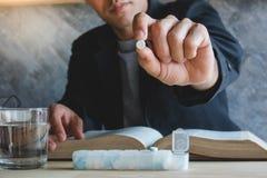 Un hombre que lleva a cabo una medicina con la caja del piil y el vidrio de agua Foto de archivo libre de regalías