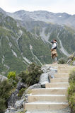 Un hombre que lleva la foto a lo largo del rastro que camina los lagos y la opinión azules del glaciar de Tasman, Aoraki/cocinero Imágenes de archivo libres de regalías