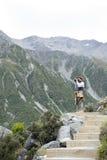 Un hombre que lleva la foto a lo largo del rastro que camina los lagos y la opinión azules del glaciar de Tasman, Aoraki/cocinero Imagen de archivo