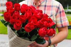 Un hombre que lleva un ramo enorme de rosas rojas Imagen de archivo