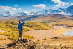 Un hombre que mira las montañas y un lago abajo de punto de vista Fotos de archivo
