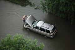 Un hombre que mira su coche con el motor parado en agua Fotos de archivo
