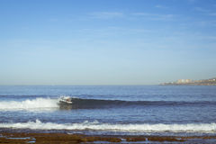 Un hombre que monta las ondas en la resaca Fotos de archivo libres de regalías