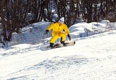 Un hombre que monta una snowboard Imagen de archivo libre de regalías