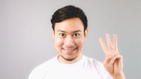Un hombre que muestra a muestra de la mano la tercera cosa Imagen de archivo