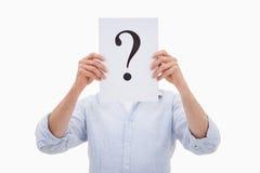 Un hombre que oculta su cara detrás de un signo de interrogación Imagenes de archivo