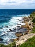 Un hombre que pesca en un cielo azul y un mar de la playa rocosa imagen de archivo