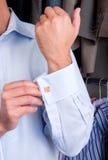 Un hombre que pone en sus vínculos de puño Foto de archivo libre de regalías