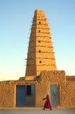 Un hombre que recorre delante de la mezquita de Agadez foto de archivo