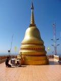 Un hombre que ruega cerca de stupa de oro en un templo budista en Tailandia Fotografía de archivo libre de regalías