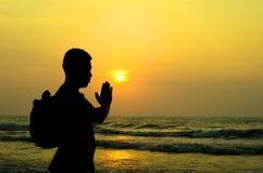 Un hombre que ruega delante de una salida del sol de oro en la playa Fotografía de archivo libre de regalías