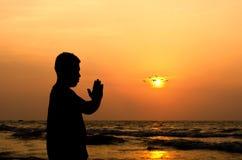 Un hombre que ruega delante de una salida del sol de oro en la playa Fotos de archivo