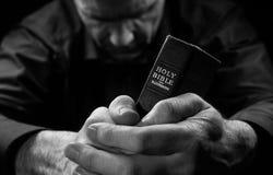 Un hombre que ruega sosteniendo una biblia. Fotografía de archivo