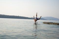 Un hombre que salta en el agua Fotografía de archivo