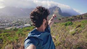 Un hombre que señala en la montaña y que agita en la cámara almacen de metraje de vídeo