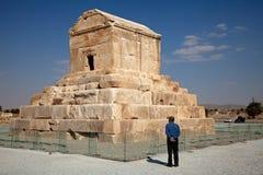 Un hombre que se coloca al lado de Cyrus Tomb en Pasargad de Irán imagen de archivo libre de regalías