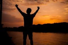 Un hombre que se coloca en el fondo de la puesta del sol Imagen de archivo libre de regalías