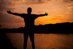 Un hombre que se coloca en el fondo de la puesta del sol Imagenes de archivo