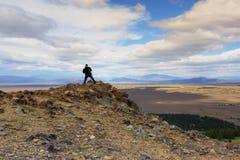 Un hombre que se coloca en el pico del punto de observación Imagenes de archivo